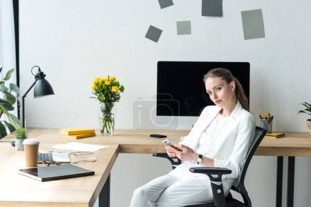 businesswoman in stylish suit with smartphone at workplace with laptop in office