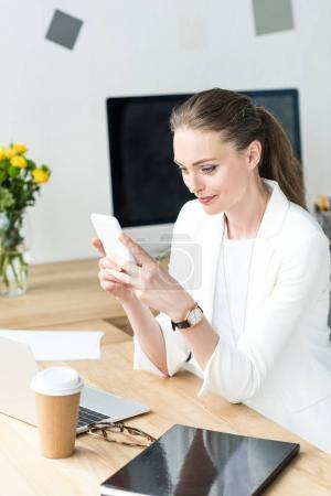 smiling businesswoman in stylish suit using smartphone at workplace in office