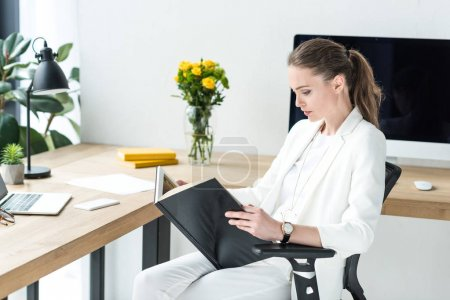 side view of focused businesswoman reading book at workplace in office