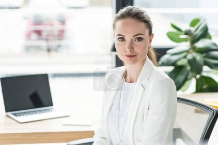 Photo for Portrait of smiling beautiful businesswoman in white suit at workplace with laptop in office - Royalty Free Image