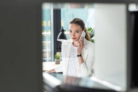 Photo pour Mise au point sélective de femme d'affaires en costume élégant parler sur smartphone au lieu de travail au bureau - image libre de droit