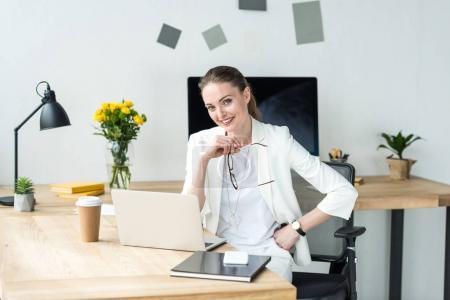 Photo pour Belle femme d'affaires en costume blanc, assis au milieu de travail avec ordinateur portable et de café pour aller au bureau de sourire - image libre de droit