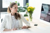 businesswoman looking at computer screen at workplace with bouquet of flowers in vase in office