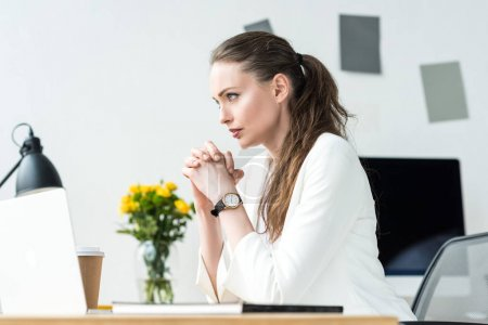 side view of thoughtful businesswoman in white suit looking away at workplace in office
