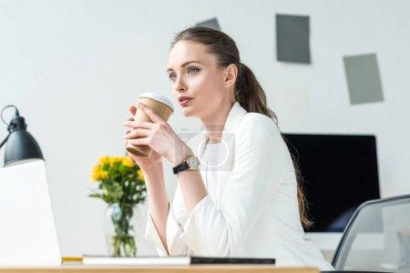 Photo pour Vue latérale de femme d'affaires coûteuse avec café pour aller sur le lieu de travail au bureau - image libre de droit