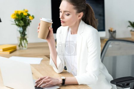 businesswoman with coffee to go working on laptop at workplace in office