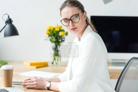 Photo for Side view of beautiful businesswoman in white suit and eyeglasses at workplace in office - Royalty Free Image