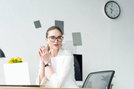Photo for Portrait of businesswoman in white suit and eyeglasses at workplace with laptop in office - Royalty Free Image