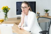 portrait of thoughtful businesswoman in eyeglasses at workplace with laptop in office