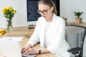 focused businesswoman in eyeglasses working on laptop at workplace in office