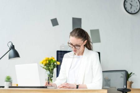 portrait of focused businesswoman doing paperwork at workplace with laptop in office