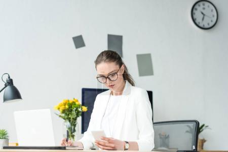 Photo for Portrait of businesswoman using smartphone while doing paperwork at workplace in office - Royalty Free Image