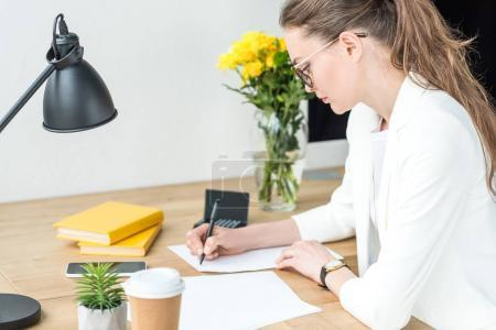 side view of businesswoman in eyeglasses doing paperwork at workplace in office