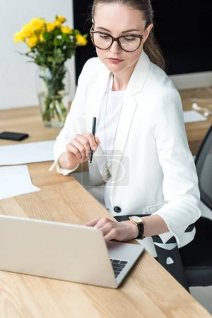 portrait of businesswoman in eyeglasses typing on laptop at workplace in office