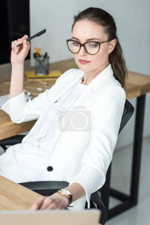 selective focus of businesswoman in eyeglasses working on laptop at workplace in office