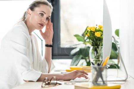 side view of pensive businesswoman at workplace with computer screen in office