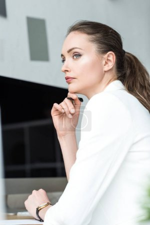 side view of beautiful pensive businesswoman in white suit looking away in office