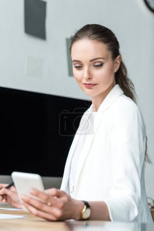 selective focus of beautiful businesswoman using smartphone at workplace in office