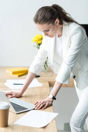 concentrated businesswoman looking at laptop screen at workplace in office