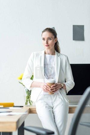 Photo pour Femme d'affaires pensif avec café pour aller debout au milieu de travail au bureau - image libre de droit
