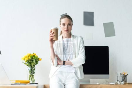 portrait of businesswoman with coffee to go leaning at table with blank computer screen and bouquet of flowers in vase in office