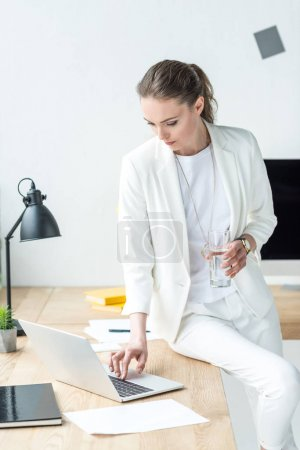 businesswoman with glass of water working on laptop at workplace in office