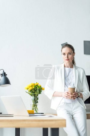 portrait of pensive businesswoman with coffee to go in office