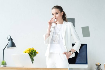 portrait of businesswoman drinking water from glass at workplace in office