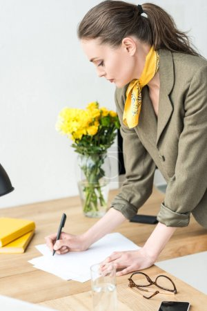 attractive stylish businesswoman taking notes at workplace