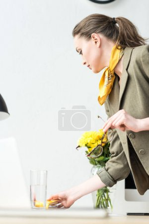 side view of stylish businesswoman holding eyeglasses and reaching for glass of water in office