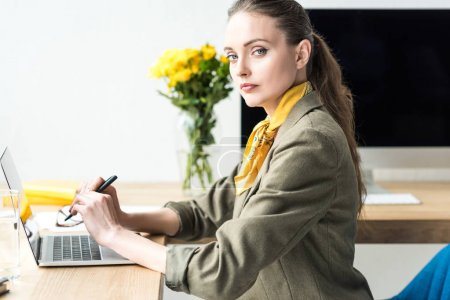 beautiful stylish businesswoman looking at camera while working with laptop in office