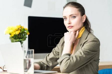 attractive businesswoman using laptop while sitting at workplace