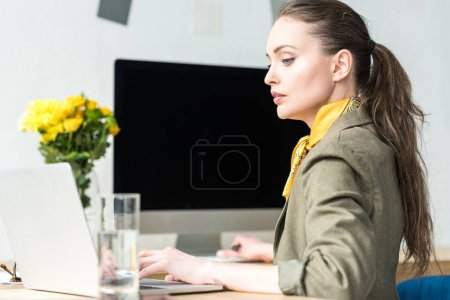 side view of attractive stylish businesswoman using laptop in office