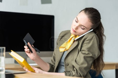 businesswoman talking by smartphone while holding book and calculator at workplace