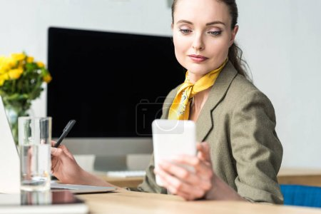beautiful smiling middle aged businesswoman using smartphone at workplace
