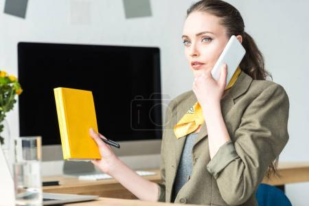 beautiful stylish businesswoman holding book and talking by smartphone at workplace