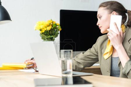 Foto de Hermosa empresaria hablando por teléfonos inteligentes y tomar notas mientras trabaja en la oficina - Imagen libre de derechos