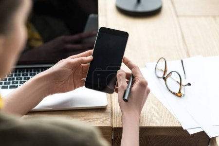 Photo for Cropped shot of businesswoman using smartphone with blank screen at workplace - Royalty Free Image
