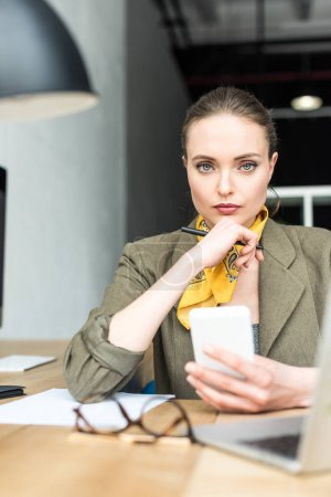 beautiful mid adult businesswoman using smartphone and looking at camera in office