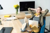 stylish businesswoman with laptop sitting with hands behind head and looking away in office