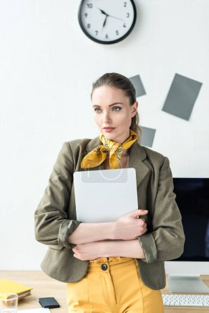 Photo for Beautiful stylish businesswoman holding laptop and looking away in office - Royalty Free Image