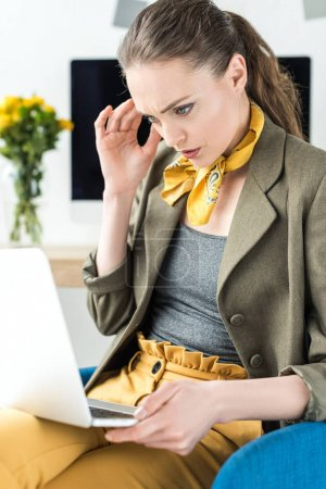 concentrated businesswoman using laptop while sitting in office