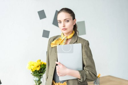 beautiful stylish businesswoman holding laptop and looking at camera in office
