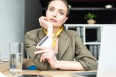 pensive stylish businesswoman holding credit card while sitting at workplace