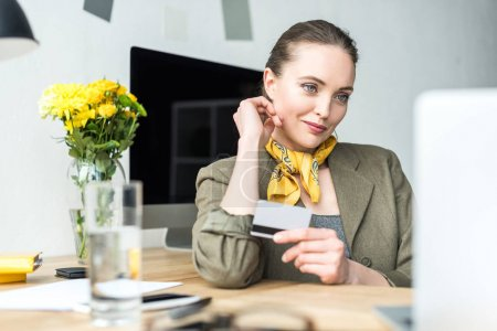 smiling stylish businesswoman holding credit card and looking at laptop in office