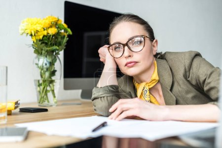 pensive businesswoman in eyeglasses leaning at table and looking away in office