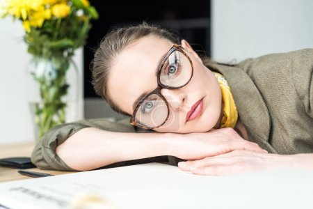 portrait of beautiful businesswoman in eyeglasses looking at camera while leaning at table in office