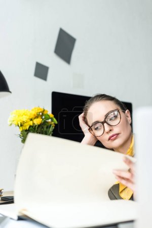 close-up view of bored businesswoman in eyeglasses working with papers at workplace