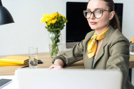 attractive smiling businesswoman in eyeglasses looking away while sitting at workplace