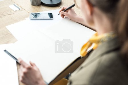 Photo for Selective focus of businesswoman in eyeglasses taking notes at workplace - Royalty Free Image